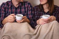年轻人递两个杯子热的格子花呢披肩女性人咖啡衬衣笼子 库存图片
