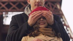年轻人通过盖她的眼睛使他的女朋友惊奇用手,愉快的日期 股票录像