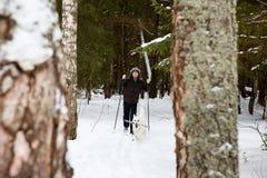 年轻人速度滑雪在有白色狗的森林里 库存照片