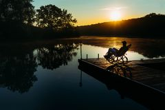 年轻人遇见黎明在扶手椅子坐码头 假日休息的休闲概念 库存照片