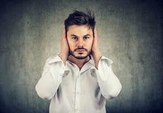 年轻人避免噪声的覆盖物耳朵 免版税库存照片