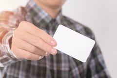 年轻人陈列,给从他的嘲笑设计样板的衬衣的口袋的空白的名片 免版税库存图片