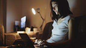 年轻人集中了在家使用便携式计算机的妇女和输入消息夜间 免版税图库摄影