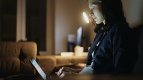 年轻人集中了在家工作在夜间的妇女使用便携式计算机和键入的消息 股票视频