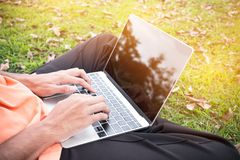 年轻人顶视图在公园坐与膝上型计算机的绿草 库存照片