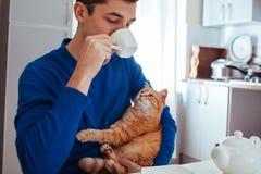 年轻人饮用的茶的画象与一只猫的在厨房 库存图片