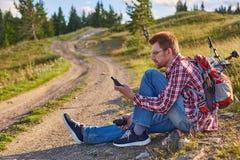 年轻人骑自行车者坐在土路边缘 库存照片