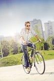 年轻人骑马自行车 库存照片