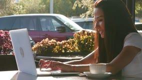 年轻人,享用一杯咖啡在咖啡馆的愉快的可爱的妇女,键入在膝上型计算机 股票视频