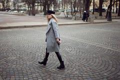 年轻人,熟悉内情和有吸引力白肤金发一个时髦的帽子的走在城市附近,女孩和一件灰色外套 行人交叉路 库存照片