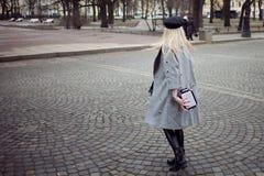 年轻人,熟悉内情和有吸引力白肤金发一个时髦的帽子的走在城市附近,女孩和一件灰色外套 行人交叉路 图库摄影