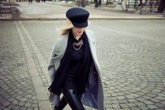 年轻人,熟悉内情和有吸引力白肤金发一个时髦的帽子的走在城市附近,女孩和一件灰色外套 行人交叉路 免版税库存照片