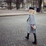 年轻人,熟悉内情和有吸引力白肤金发一个时髦的帽子的走在城市附近,女孩和一件灰色外套 行人交叉路 免版税库存图片