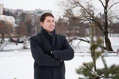 年轻人,走在冬天公园的商人 免版税库存图片