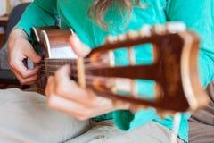 年轻人` s在家递播放声学吉他尤克里里琴 演奏在关闭的一个人尤克里里琴看法 库存图片