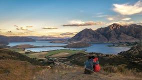 年轻从山的顶端夫妇观看的日落 库存照片
