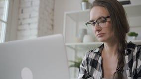 年轻企业主女性与坐在家庭内部的桌上的膝上型计算机一起使用 股票视频