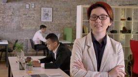 年轻企业亚裔妇女用点头横渡的手看在照相机在现代办公室和,微笑,黑和 股票录像