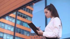 年轻企业女孩做在站立近的商业中心的文件的笔记 慢的行动 股票录像