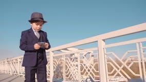 年轻企业男孩在从桥梁的黑衣服和帽子投掷的金钱 废金钱 股票视频