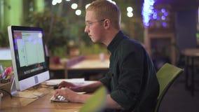 年轻体贴的人画象坐在他的在现代计算机前面的工作场所的玻璃的在大办公室键入 股票视频