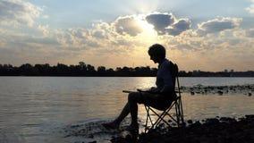 年轻作家在河岸的水中坐和微笑并且赤足移动他的 股票视频