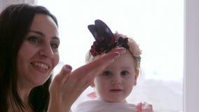 年轻使用与活蝴蝶的母亲和小女儿在手上在慢动作的室 影视素材