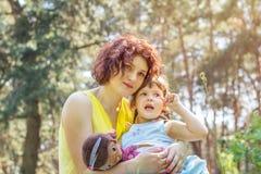 年轻使用在公园的母亲和小女儿在一个夏天 免版税库存图片