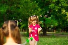 年轻使用在有肥皂泡的公园的母亲和小女儿 库存照片