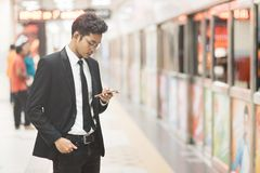 年轻使用智能手机的行家亚洲商人,当等待火车在地铁时 无线技术的概念,流动 库存照片
