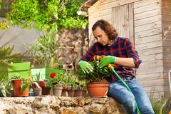 年轻使用橡胶软管的人浇灌的盆的花 免版税库存照片