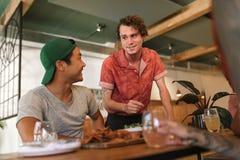 年轻侍者谈话与一个小组微笑的小餐馆顾客 免版税库存图片