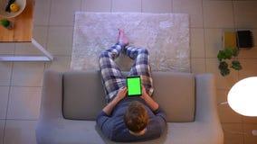 年轻便服男性看着电视和使用有绿色屏幕的片剂特写镜头顶面射击坐长沙发 股票录像