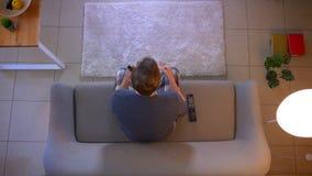 年轻便服男性观看的体育特写镜头顶面射击在电视的坐变得的长沙发愉快和 股票录像