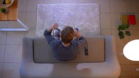 年轻便服男性观看的足球赛特写镜头顶面射击在电视的坐得到的长沙发激发 影视素材