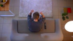 年轻便服男性观看的足球赛特写镜头顶面射击在电视的坐得到的长沙发激发 股票视频