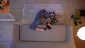 年轻便服男性购物特写镜头顶面射击网上与在电话的信用卡坐地板 股票视频