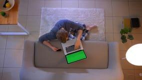 年轻便服男性购物特写镜头顶面射击网上与在膝上型计算机的信用卡坐地板 股票录像