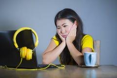 年轻俏丽和乏味亚裔韩国学生女孩与看起来的便携式计算机一起使用不快乐和困举行的面孔用手 免版税库存照片