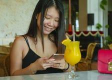 年轻俏丽和愉快亚洲中国妇女坐轻松在咖啡馆或旅馆餐馆使用社会媒介互联网应用程序  库存图片