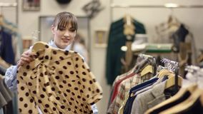 年轻俏丽妇女寻找在服装店的衣裳和采取精密衬衣,但是放回它 股票录像