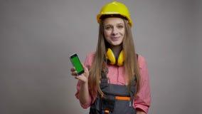 年轻俏丽的女孩建造者显示她的电话色度屏幕,微笑,通信概念,灰色背景 股票视频