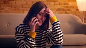 年轻俏丽的女孩特写镜头画象有电话和谈快乐坐地板在舒适 股票视频