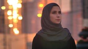 年轻俏丽的女性特写镜头画象看起来的hijab的直接与都市城市和发光的大厦在 免版税库存图片