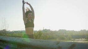 年轻俏丽的女运动员参与健身本质上 女孩执行在城市之外的锻炼 steadicam射击 影视素材
