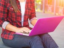 年轻俏丽的妇女与膝上型计算机坐outsite工作的台阶 免版税图库摄影