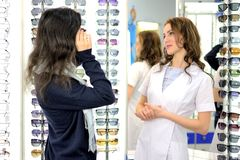 年轻俏丽的妇女在一家eyewear商店试穿太阳镜在售货员的帮助下 免版税库存图片