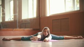 年轻俏丽的妇女坐执行分裂的瑜伽席子-弯下来对地板 影视素材