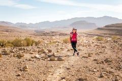 年轻俏丽的妇女常设石沙漠足迹,摆在照相机 库存照片