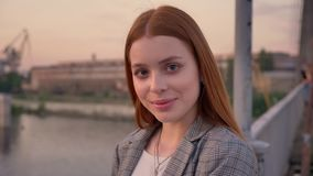 年轻俏丽的妇女画象有站立在桥梁和调查照相机的姜头发的,微笑,日落 股票视频